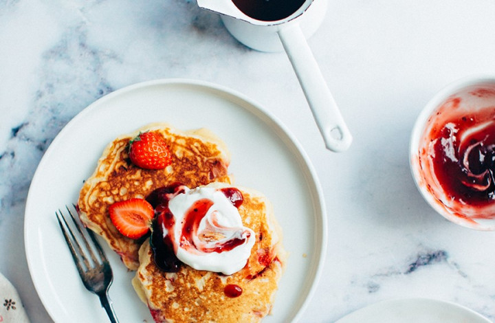 Pancakes with whipped cream and strawberry jam